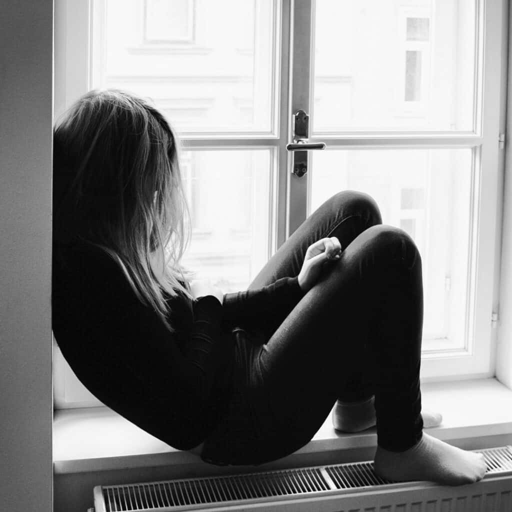Vrouw somber zittend in raamgat